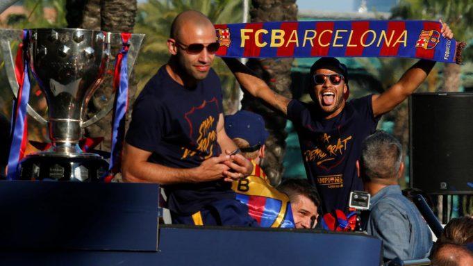Pemain Barcelona, Javier Mascherano (kiri) dan Neymar, mengikuti pawai dengan bus mengililingi kota Barcelona untuk merayakan gelar La Liga ke-24 bagi Barcelona