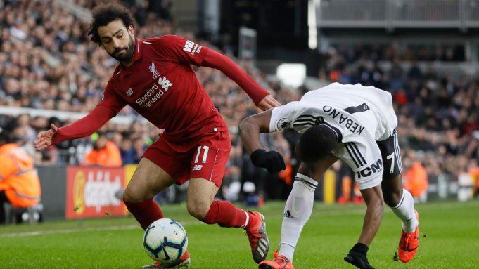 Pemain Liverpool Mohamed Salah (kiri) melewati pemain Fulham Neeskens Kebano pada laga pekan ke-31 Liga Inggris di Stadion Craven Cottage, London, Minggu (17/3). Liverpool menang tipis 2-1.