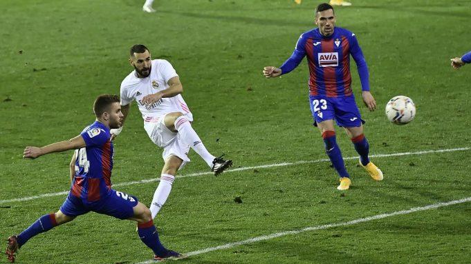 Penyerang Real Madrid, Karim Benzema melakukan tendangan dibayangi pemain Eibar pada laga lanjutan Liga Spanyol di Stadion Ipurua, Senin dinihari WIB (21/12/2020). Benzema menjadi pahlawan dalam kemenangan Madrid karena menciptakan satu gol dan dua assist di laga tersebut.