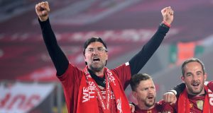 Pelatih Liverpool, Jurgen Klopp, merayakan trofi juara Premier league 2019-2020 di Stadion Anfield, Kamis (23/7/2020) dini hari WIB. Prosesi angkat trofi juara ini dilakukan usai pertandingan Liverpool melawan Chelsea.