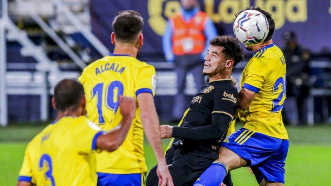 Penyerang Barcelona, Philippe Coutinho, duel udara dengan pemain Cadiz, Jairo Izquierdo, pada laga Liga Spanyol di Stadion Ramon Carranza, Minggu (6/12/2020). Barcelona takluk dengan skor 1-2.